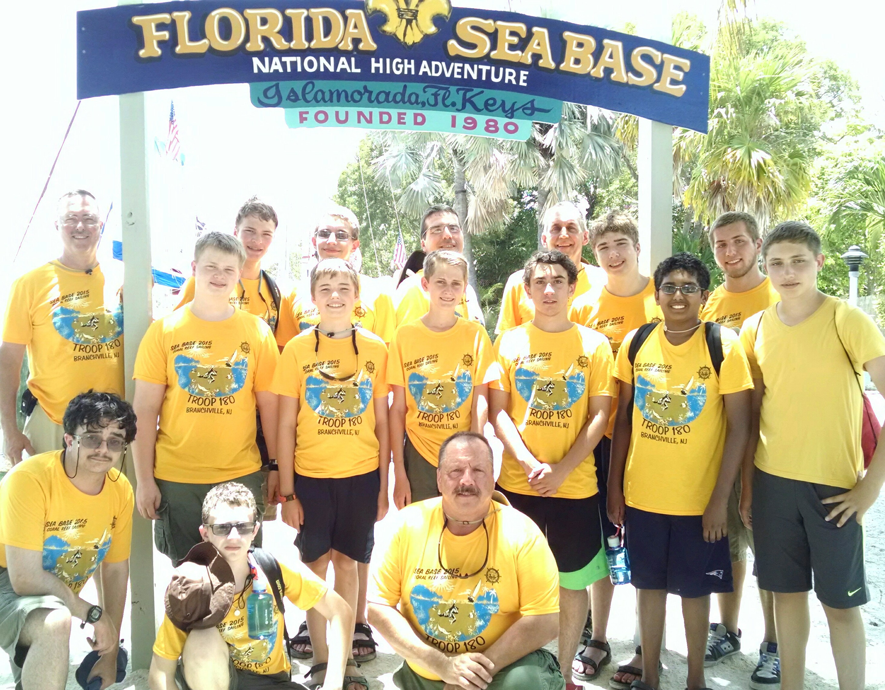 Troop 180 is shown wearing their gold Classic Fit Performance T-Shirts from Class B in front of the Florida Sea Base Camp
